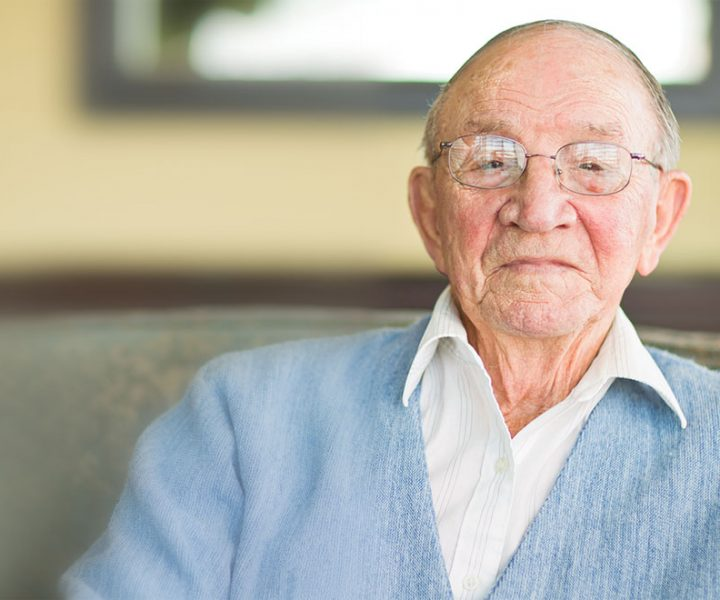 Elderly man sitting on couch in home
